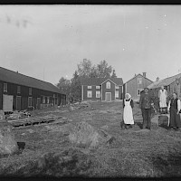 The cottage of Anders Snygg and adherent outbuildings. The people living on the farm gathered in the yard. Replot in 1922.   Photographer: Curt Segerstråle.  Archive collection: The Society of Swedish Literature in Finland (SLS), sls.finna.fi SLS 388_76