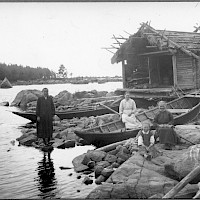 Women at a fishing harbour in the village of Västerö, Maxmo. Boats and sheds by the shore. 1920's–1930's.   Photographer: Erik Hägglund.  Archive collection: The Society of Swedish Literature in Finland (SLS), sls.finna.fi SLS 865 B 133