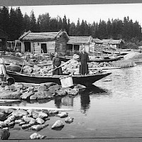 Fishing harbour in the village of Österö, Maxmo. Three women by the shore, boats and sheds. Photographer: Erik Hägglund. Archive collection: The Society of Swedish Literature in Finland (SLS), sls.finna.fi SLS 865 B 179