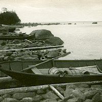Fishing harbour in the village of Österö, Maxmo. Boats pulled ashore on logs, sheds.   Photographer: Erik Hägglund.  Archive collection: The Society of Swedish Literature in Finland (SLS), sls.finna.fi SLS 865 B 180