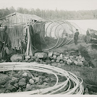A fyke net for herring is being repaired. Fishing village off the village of Rödsö, Karleby, in 1924.   Photographer: Curt Segerstråle.  Archive collection: The Society of Swedish Literature in Finland (SLS), sls.finna.fi SLS 388_118